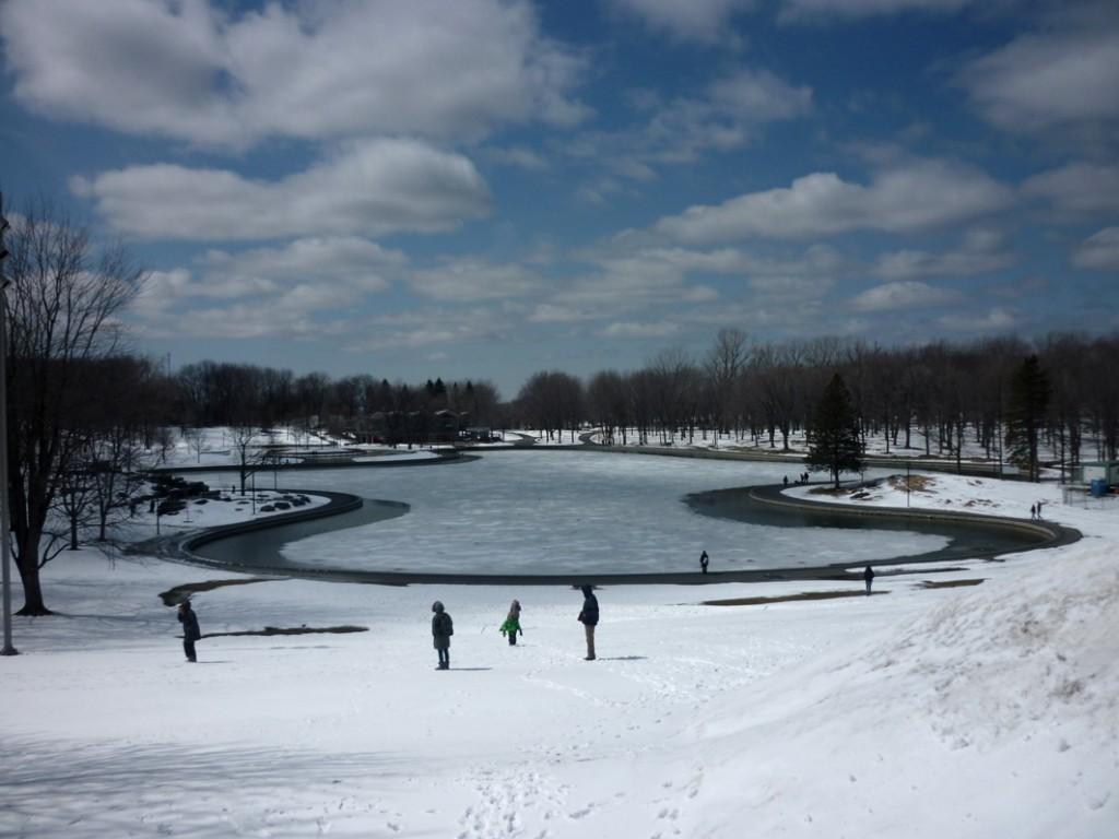 photo du Mont Royal et du lac des castors au cœur de Montréal. Le lac fait se rejoindre le ciel bleu et le parc enneigé.